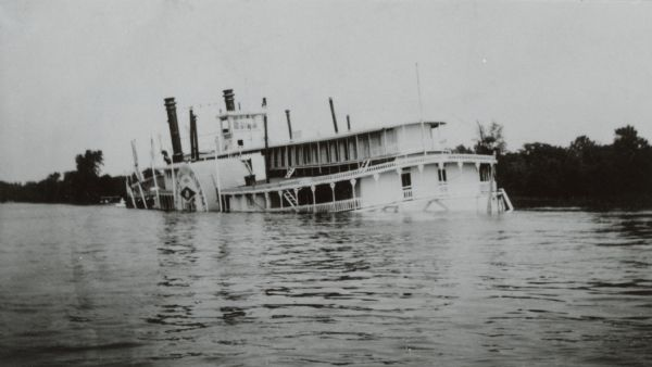 Sidewheel packet <i>Quincy</i>, sinking. Only her two upper decks are above water. Trempealeau Mountain is in the background. Later renamed the <i>J.S.</i>