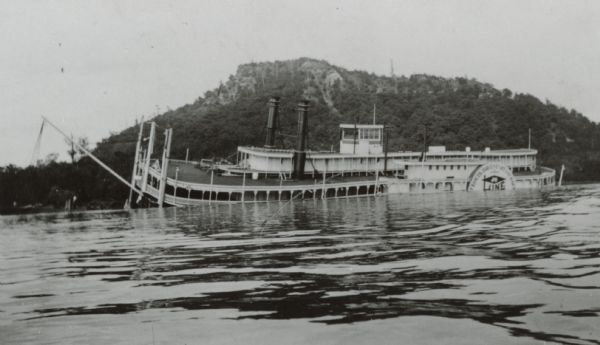 Side view of the sidewheel packet, <i>Quincy</i>, sinking in 1906. Only her two upper decks are above water. Trempealeau Mountain is in the background. Later renamed the <i>J.S.</i>