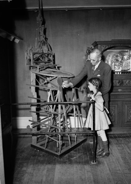 "Photograph of clock made by John Muir while a student at the University of Wisconsin in 1860. A young girl, and Charles Brown of the Wisconsin Historical Society staff, look at the John Muir clock on display at the State Historical Society of Wisconsin. John Muir (1838-1914) was America's most famous and influential naturalist and conservationist. He is one of California's most important historical personalities. He has been called ""The Father of our National Parks,"" ""Wilderness Prophet,"" and ""Citizen of the Universe."""