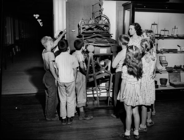 "Photograph of clock made by John Muir while a student at the University of Wisconsin in 1860. Children are looking at the John Muir clock in the museum at The State Historical Society. John Muir (1838-1914) was America's most famous and influential naturalist and conservationist. He is one of California's most important historical personalities. He has been called ""The Father of our National Parks,"" ""Wilderness Prophet,"" and ""Citizen of the Universe."""