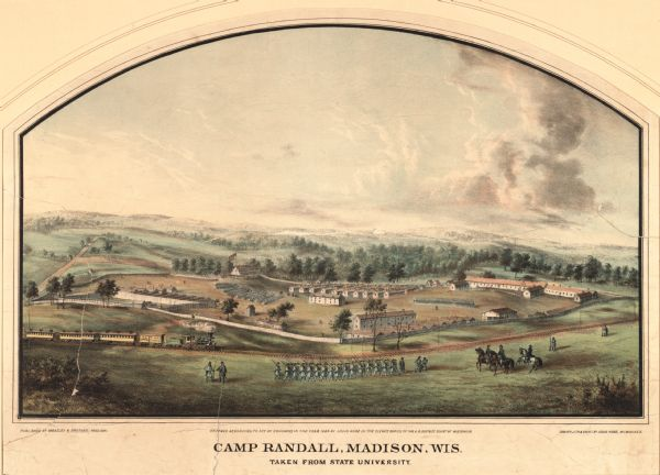 Lithograph of Camp Randall, where the majority of Wisconsin's soldiers were trained and mustered into the Union Army.  This view, which was taken from Bascom Hill looking southwest, shows a railroad track in the foreground which followed the route along University Avenue still used today.  Inside the fenced enclosure barracks, prison yard and guard house, officers quarters, stables, and (the large building on the right) a hospital.