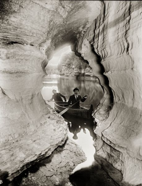 Two men navigating their canoe through caves at the Wisconsin Dells.