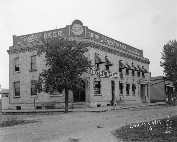 Exterior view of the Hotel Nelson, a brick building with Schlitz Beer signs on top.