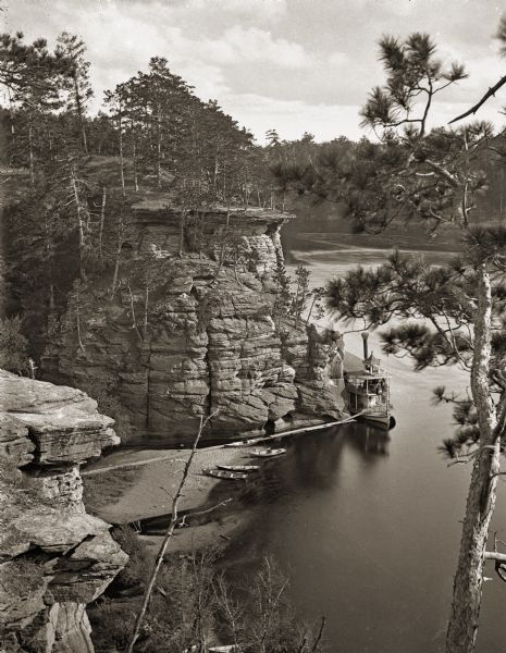 Mouth of Witches' Gulch and downstream, viewed from cliff. Steamboat <i>Alexander Mitchell</i> at mouth of gulch. Four canoes are on shore.