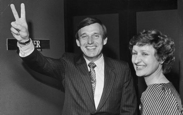 Governor Martin Schreiber displays the V for victory sign as his wife stands with him, smiling.