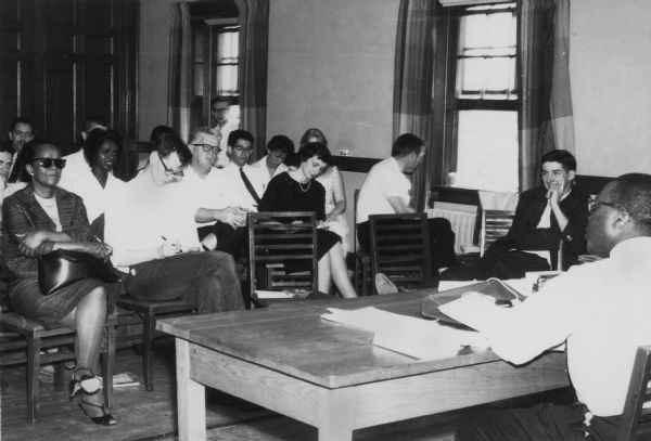 Student Leadership Conference, May 4-6, including Ella Baker (front row, far left), Carl Braden (second row, hands clasped around knees), Anne Braden (second row, black dress), and Tom Hayden (right of window in dark jacket).