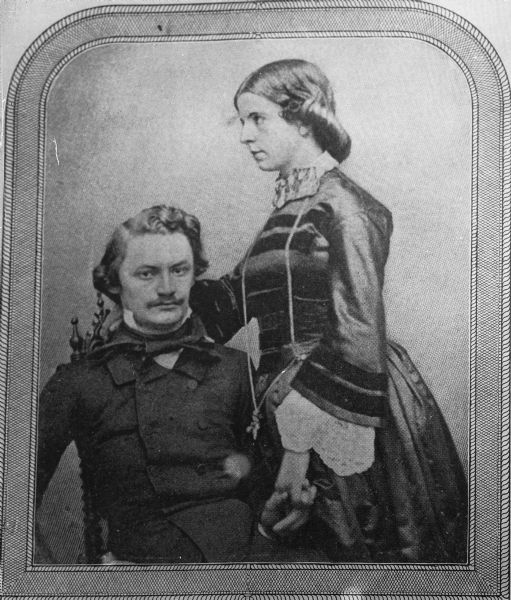 Formal studio portrait showing Carl Schurz seated and Margarethe  [Meyer] Schurz,(Mrs. Carl Schurz) posed standing next to him.