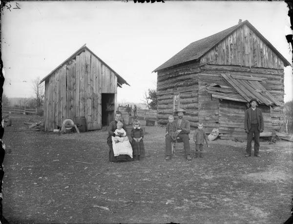Man and woman posing sitting, each holding a child in their lap, and a young man, girl, and a boy holding a toy horn, are posing standing. The group is posing in the yard in front of a log house and farm building. According to Bonnie Evans of Cataract, Wisconsin, this is the Chas. Koehler family, and the man on the right is Gust Jones, a nephew.