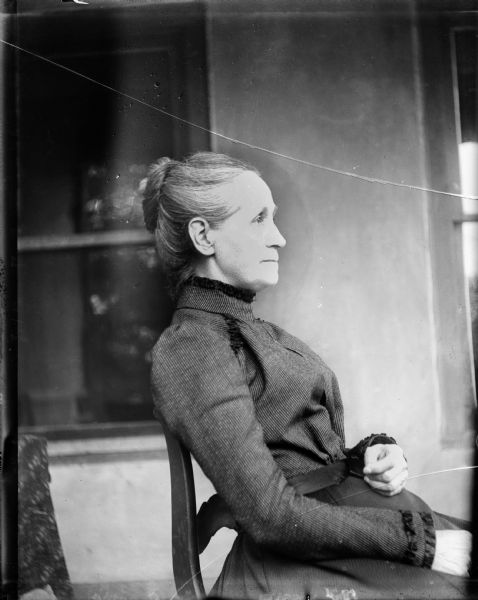 Informal portrait of a woman seated in a chair.