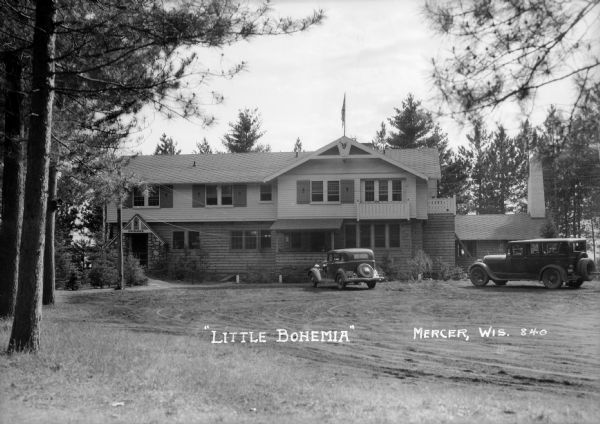 Exterior view of Little Bohemia Restaurant and Lodge with multiple vehicles parked out front.