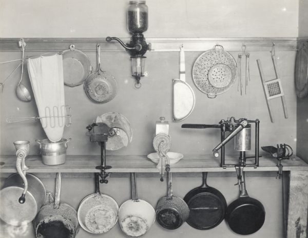 Several kitchen implements, including some skillets, sauce pans, a coffee grinder, and a colander.