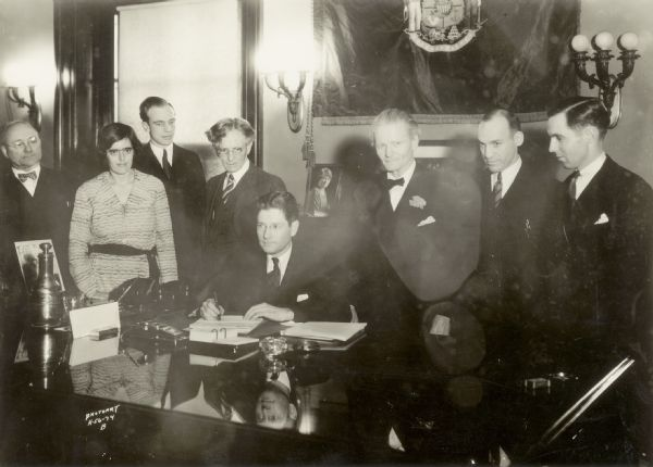 Governor Philip La Follette signing Wisconsin's pioneer unemployment compensation law. From left to right are Henry Ohl, Elizabeth Brandeis, Paul A. Raushenbush, John R. Commons, Governor La Follette, Henry A. Huber, Harold M. Groves, and Robert A. Nixon.