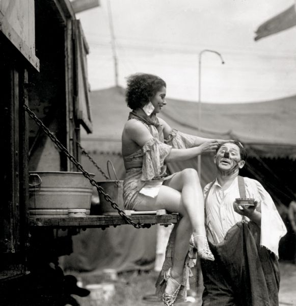 Circus performer Harriet Hodgini, sits on the gate of a truck helping Otto Griebling, a circus clown, apply his makeup.