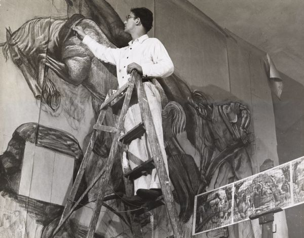 Santos Zingale (1908-1999), then an unemployed artist, working on the cartoon phase of a WPA mural he was painting in Racine. The preliminary sketch from which he is working can be seen at the lower right. In 1946 Zingale joined the University of Wisconsin Art Department, where he continued to teach until his retirement in 1946.