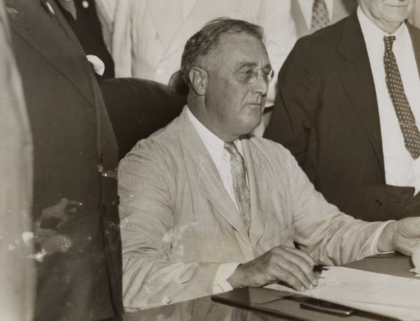 President Franklin D. Roosevelt about to sign the Social Security Act of 1935.