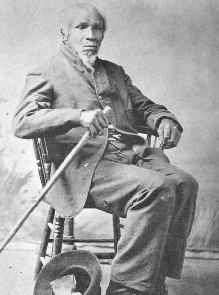 Portrait image of Stephen Bonga (1799-1884) pictured with a hat and walking stick.