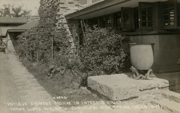 View of the entrance court of Taliesin, Frank Lloyd Wright's residence and studio, as it appeared after its completion in May of 1911 and before its partial destruction by fire in August of 1914. Taliesin is located in the vicinity of Spring Green, Wisconsin.