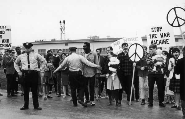 Opponents of the War in Vietnam protesting at Truax Air Force Base.  This event, which was probably sponsored by local members of the National Coordinating Committee Against the War in Vietnam, was one of the first demonstrations against the war in Madison.