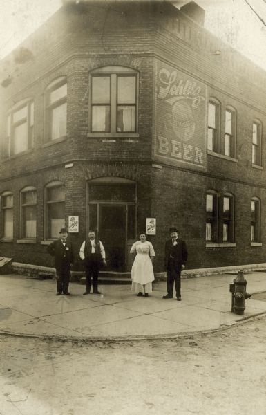 Exterior view of the bar owned by Rudolph Steinbacher at the corner of 16th Street and St. Paul Avenue.  A large sign for Schlitz beer is painted on the wall and four people, perhaps the owner and employees, are standing in front.