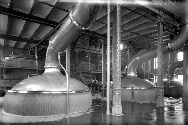 View of the brew house of the Joseph Schlitz Brewing Company. A man can be seen standing in the background.