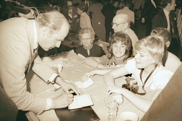 Senator Gaylord Nelson signs an autograph for an admiring voter at an agricultural conference.