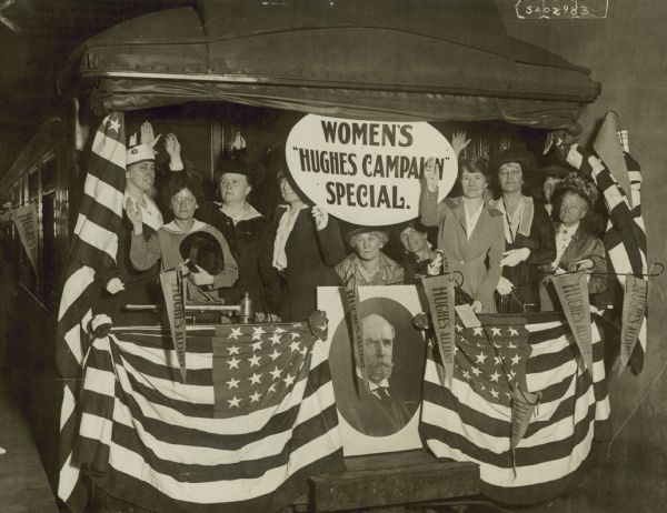 "Women who make up the Hughes Alliance, led by Mrs. Harry Payne Whitney, daughter of Cornelius Vanderbuilt Sr., pose on the back of a train draped with bunting and Charles Evans Hughes banners. There is a sign that reads ""Women's 'Hughes Campaign' Special"".  Hughes ran for president on the Republican ticket in 1916.  ""Determined that the power of women shall be felt, the national Hughes alliance arranged for a special train to carry 25 women of prominence into 31 states and more than 100 cities, in October 1916 in the interests of Hughes' campaign.  Among those invited to participate were Mary Antin, Ella Flagg Young, Edna Ferber, Gertrude Atherton, Inez Gilmore, Mary Roberts Rhinehart, Mary Shaw and Zona Gale."" from brief article in Wis State Journal 9-6-1916 p. 3"