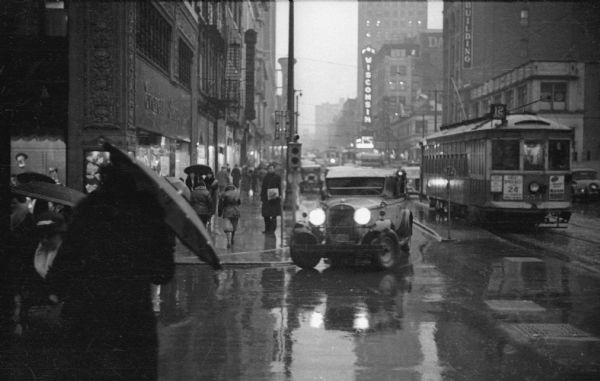 Automobile traffic, with a street railroad car in the background, on a rainy day.