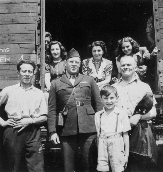 Refugees on their way to Bremerhaven, Germany to sail to the United States. The man in the center is Max Neumann, director of HIAS in Germany. On the left is the Weinschenker family. Frieda Weinschenker is seated in the train doorway on the far right and next to her is her mother Klara Weinschenker. Standing in front of Frieda is her father Chaim Weinschenker, and standing in front of him is Frieda's brother Milo Weinschenker.