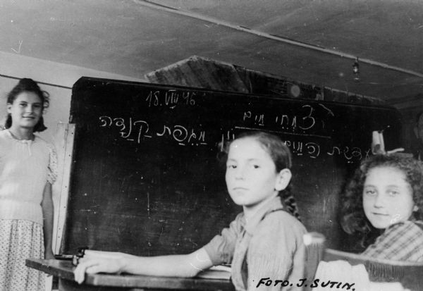 "Refugee children learning Hebrew at a displaced persons camp school; Germany.  Saul Sorrin was interviewed as part of the Wisconsin Survivors of the Holocaust Interviews project. Sorrin, born in New York in 1919, applied in 1940 for a position with the United Nations Relief and Rehabilitation Administration (UNRRA). He worked with Holocaust survivors as a supply officer for UNRAA team 560 at the Displaced Persons camp Neu Freimann Siedlung in Germany and later, at General Dwight D. Eisenhower's recommendation, Sorrin became the Area Director of the International Refugee Organization based at the Wolfratshausen DP camp in Bad Kissingen.  When asked about this image, Sorrin revealed, ""I can even see the date on this: August 18, 1946.  It's a classroom in Hebrew.  The children there--we had a strong urge to education and we had schools set up.  We had a hard put to find teachers but we found them and teaching materials.  I'm not sure which camp this is in.""  Interview by Jean Loeb Lettofsky and David Mandel, March 3, 1980."