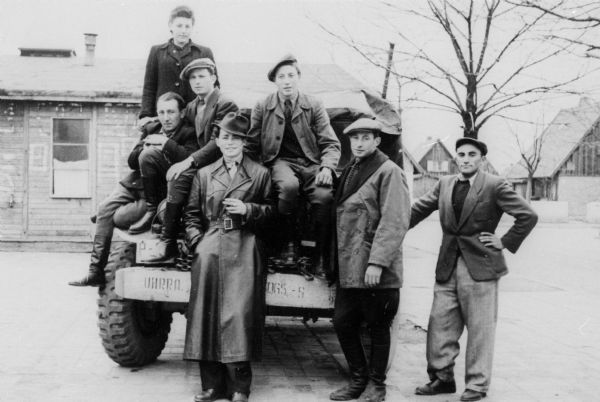 "Displaced persons camp ambulance drivers standing on a UNRRA (United Nations Relief and Rehabilitation Administration) jeep.  The man in the front, center, was a partisan during WWII; Germany.  Saul Sorrin was interviewed as part of the Wisconsin Survivors of the Holocaust Interviews project. Sorrin, born in New York in 1919, applied in 1940 for a position with the United Nations Relief and Rehabilitation Administration (UNRRA). He worked with Holocaust survivors as a supply officer for UNRAA team 560 at the Displaced Persons camp Neu Freimann Siedlung in Germany and later, at General Dwight D. Eisenhower's recommendation, Sorrin became the Area Director of the International Refugee Organization based at the Wolfratshausen DP camp in Bad Kissingen.  When asked about this image, Sorrin revealed, ""I think these fellows were our ambulance drivers, posing as a group.  We had a very big population.  People got sick.  They drove ambulances but they also drove other vehicles.  I remember this young man in his leather coat up front, and I wonder where this guy is.  He was a young guy who'd seen it all.  I remember him very clearly.  He'd been a partisan.  You can just tell by the tilt of that hat, you know, and the way he's standing there.  He had a real sense of bravado.  He used to say, 'Khaver Direktor, I could do anything.'  He went out and got that leather coat some place in Germany.  You can just tell, looking at him compared to the others that he--I don't remember his name, but these are a group of drivers in the motor pool of one of the DP camps.""  Interview by Jean Loeb Lettofsky and David Mandel, March 3, 1980."