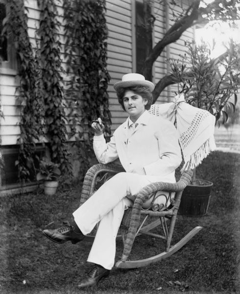 Outdoor portrait of Hattie Fels Owen wearing a white suit and hat and sitting in a wicker rocking chair. She is holding a cigar in her right hand. Behind her ivy is growing along the siding of a house. Potted plants are on the lawn.