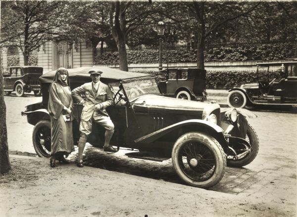 Rudolph Valentino and his wife Natacha Rambova pose with their Voisin automobile.