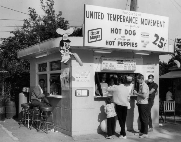"Fundraising booth of the United Temperance Movement of Wisconsin at the Wisconsin State Fair.  At that booth one could purchase soft drinks, milk, and ""first lady punch"" that supported the organization's statewide public education program.  The booth also sold Oscar Mayer brand hot dogs and ""hot puppies"" and displayed the Little Oscar sign."