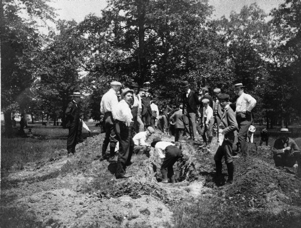 A group of children and adults excavating an oval mound in the Teller Group.