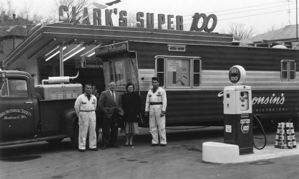 The State Historical Society of Wisconsin's Historymobile at the Clark Service Station, 2631 University Avenue. Mr. and Mrs. J.J. Tschudy (Jake and Irene), Curators of the Historymobile, center, were greeted by Dick Casper, right, manager of the station, and Jack Spahr, the attendant at left.