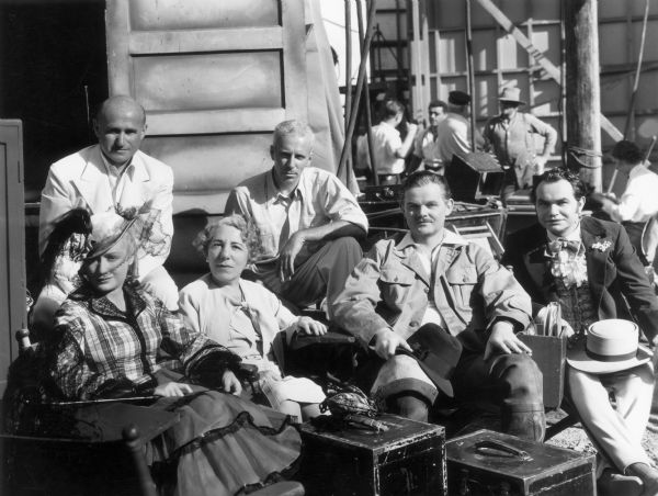 The cast of <i>Barbary Coast</i> pose on the set. In the back from left to right are: Samuel Goldwyn and Howard Hawks. In front from left to right are Miriam Hopkins, Edna Ferber, an unidentified actor, and Edward G. Robinson.