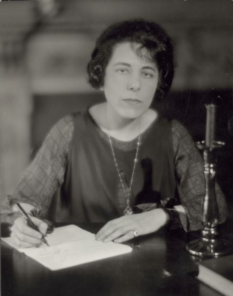 Portrait of Edna Ferber seated and writing with a pen.