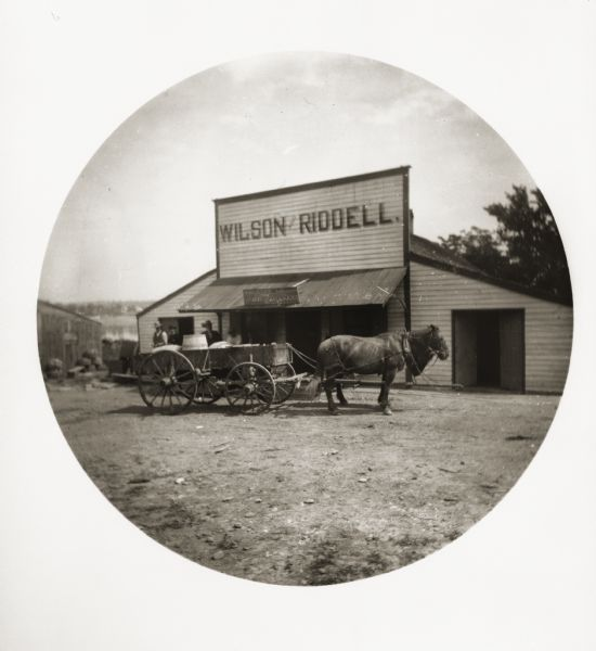 Exterior view of the Wilson Riddell general store, with a horse-drawn wagon parked in front. There is a post office and paint shop attached to the store. Several men can be seen standing behind the wagon.