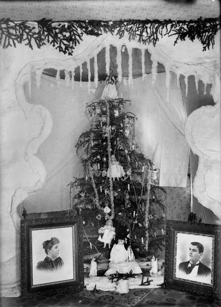 A Christmas tree decorated with ornaments and dolls is displayed with framed portraits of a man and woman on either side. A frame of artificial snow and icicles surrounds the display.