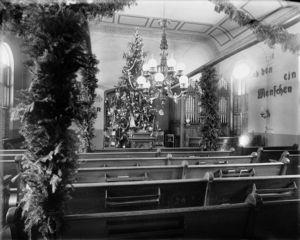 Interior view of the Old Moravian Church at 6th and Cole Streets decorated for Christmas. There is a very tall Christmas tree behind the pulpit, and other greens on posts and swags among the pews. Part of an organ can be seen on the right near the front of the church, and an ornate chandelier hangs from the ceiling.