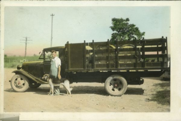 Hand-colored image of Casper Jaggi and his dog, ready to deliver a load of Swiss cheese to Monticello. He was delivering 6 tubs of Swiss cheese, each weighing 150 pounds.
