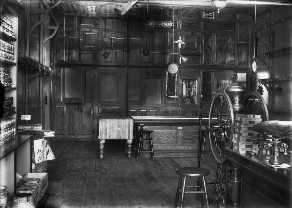 Interior view of the butcher shop section of the Fowler and Holmes Store. There is wood paneling and cabinetry throughout the room, shelving and hooks on the walls, a hanging scale, and a table scale on a table on the right.
