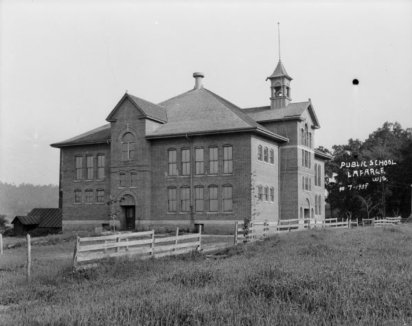 Exterior view of the public school. A large brick building with a bell tower on the roof, arched entrances, and a wooden fence along the side.