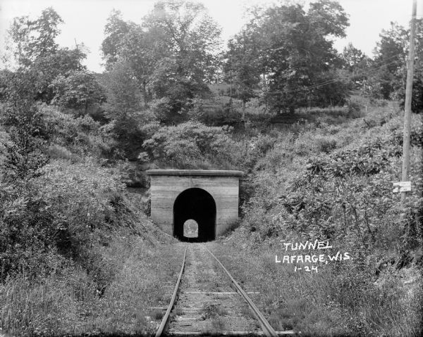 "View from railroad tracks through covered railroad tunnel in hill. A sign on a telephone pole on the right says, ""Private Property / Thoroughfare / Keep Off."" Carving above arch of train tunnel says, ""AD 1900"" (the D is backwards)."