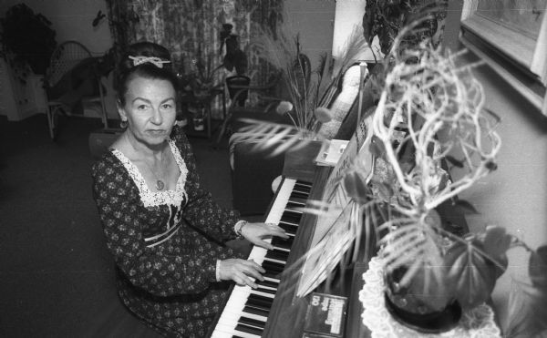 Magda Herzberger sits at the piano at her home.