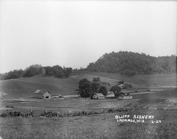 Long view of bluffs with a fence and a farm in the foreground.