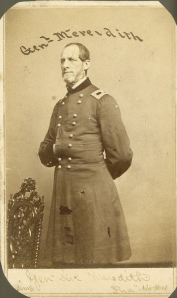 Three-quarter length studio portrait of General Meredith standing near a chair with his hand inside his jacket.