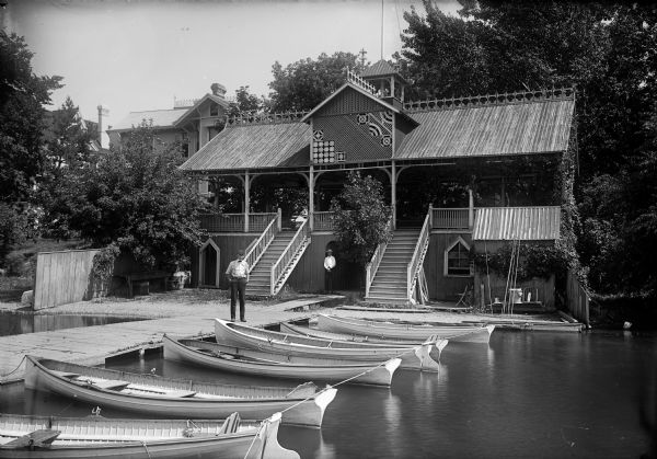View of a boathouse across from Edgerton Flats with a row of boats in front of the building. Two men stand on the pier.