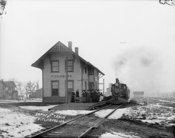 Winter scene of Fitchburg depot with train at platform, and a group of men and women waiting outdoors.