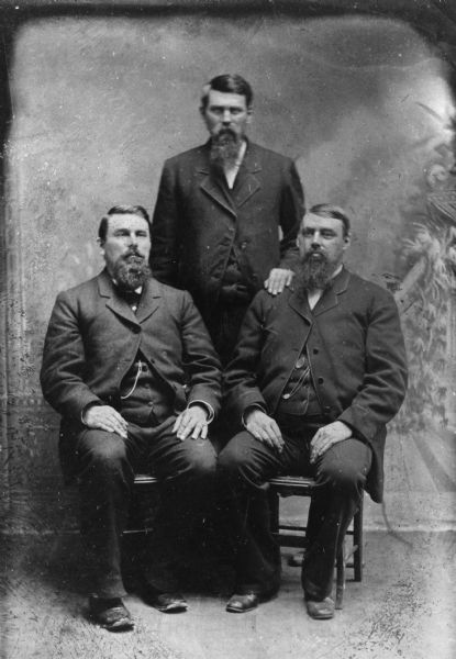 Studio portrait in front of a painted backdrop of the three Pond brothers, George F., James B., and Homer. They all have beards and moustaches. Two of the men are seated and one stands between them.